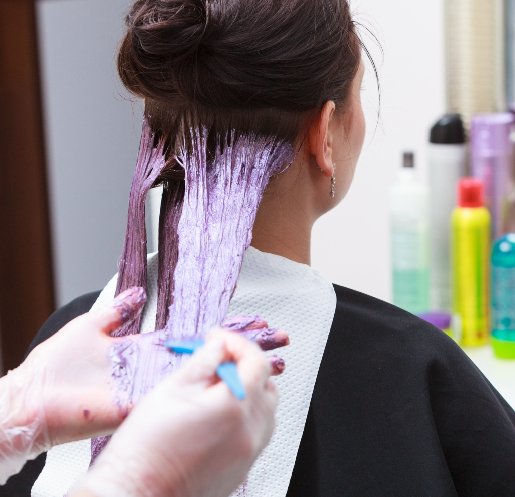 hairdresser applying color client at salon, doing hair dye